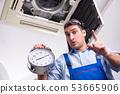 Young repairman repairing ceiling air conditioning unit  53665906