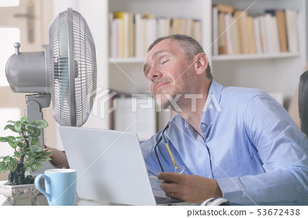 Man suffers from heat in the office or at home 53672438