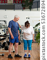 Senior woman stands on weight scale at gym. 53672894