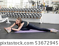 Young fit woman stretching on yoga mat at gym. 53672945