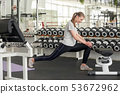 Young slim woman stretching leg at gym. 53672962