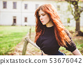 Beautiful redhead young woman outdoor portrait 53676042