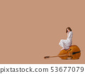 Woman musician sitting on a vintage double bass 53677079