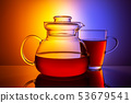Magnificent glass teapot with a cup on a multi-colored background. 53679541