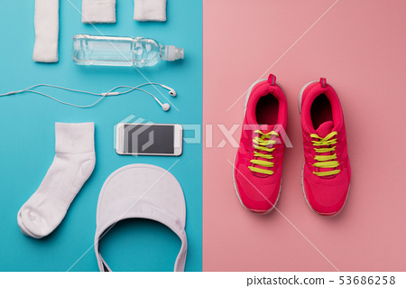 A studio shot of running shoes and other sport equipment on color background. 53686258