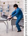 Young employee making copies at copying machine  53689939