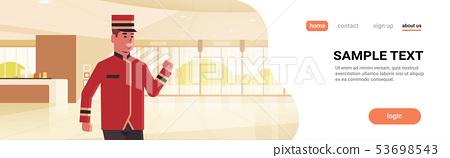 happy bellman male worker in uniform hotel service concept modern reception area lobby interior 53698543