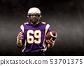 American football player posing with ball on black background 53701375