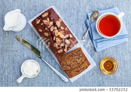Banana, carrot, apple cake, loaf with chocolate and cup of tea on grey textile background. Top view. 53702252