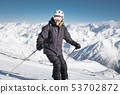 A bearded male skier in a helmet and a ski mask is standing on skis against the background of snow 53702872
