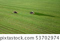 two tractors mows the grass on a green field 53702974