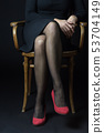 Body language - Woman is sitting with legs crossed 53704149
