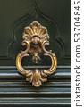 Detail of a bronze metal knocker on a wooden door of house 53704845