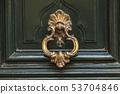 Detail of a bronze metal knocker on a wooden door of house 53704846