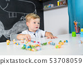 Portrait of cute toddler boy playing with toys at the desk at home. 53708059