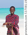 Traditonaly dressed maasai black man on picture perfect tropical Paje beach, Zanzibar, Tanzania 53708119