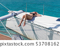 Woman relaxing on a summer sailing cruise, sitting on a luxury catamaran near picture perfect white 53708162