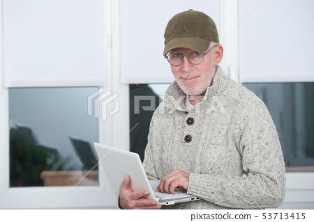 mature man with  baseball cap using a laptop 53713415