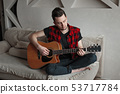 Handsome man playing the classical guitar 53717784