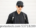 Handsome man in black clothes and stylish cap 53718289
