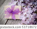 Gift box with purple bow and lilac on wood 53718672