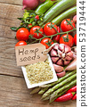 Raw organic hemp seeds with a label and vegetables 53719444
