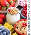 Jar of fresh yogurt, berries, muesli and measuring 53719554