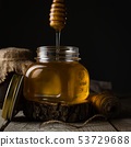 Golden honey in glass jar with dipper 53729688