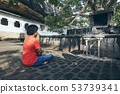 Buddhist praying against cave temple 53739341