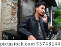 Asian man talking business on mobile phone. 53748144