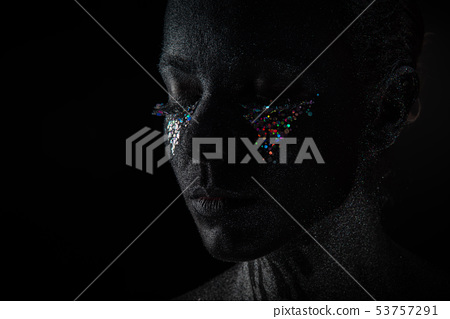 Girl in black makeup with sparkles 53757291