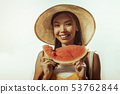 Close-up face portrait of woman keeping watermelon piece in hands. 53762844