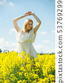 Young woman in yellow oilseed rape field stretch oneself outdoor 53769299