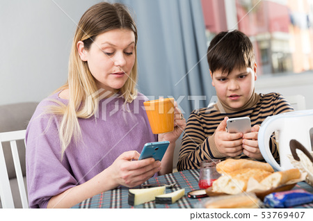 Portrait of young woman and using phones during breakfast at table 53769407