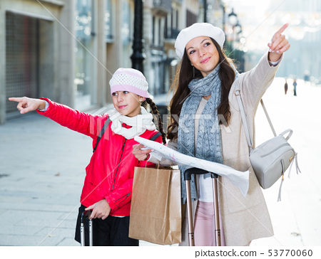 girl with mother holding map outdoors 53770060