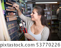 Smiling woman customer shopping various pencils 53770226