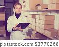 Female worker transporting cart cardboard cases 53770268