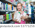 Young girl holding a lot of hair mask and shower gel 53773256