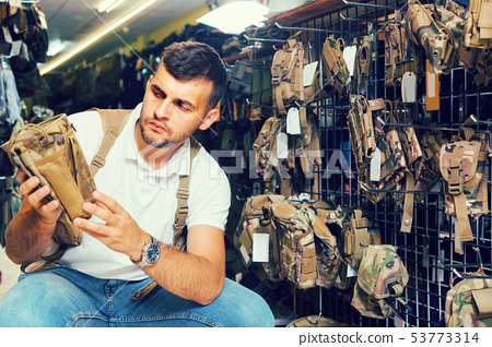 guy looking holster for pneumatic weapon in army store 53773314