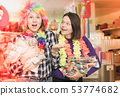 Girls with confetti in festival accessories shop 53774682