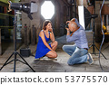 Professional photo shooting outdoors. Attractive female model posing to photographer on city street 53775570