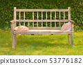 Ancient wooden bench in a garden with two straw 53776182