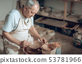 High angle of mature craftsman making clay bowl in potter's studio 53781966