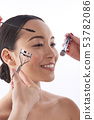 Hands of beauticians applying makeup on the face of Asian woman 53782086