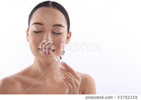 Peaceful woman enjoying her new shiny transparent lipstick 53782158