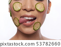 Woman licking slice of cucumber on her cheek 53782660