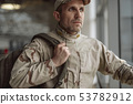 Waist up of serious American soldier in camouflage looking away 53782912