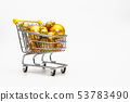 Shopping trolley full of gold Christmas balls 53783490