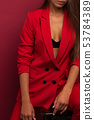Girl in a red suit with a beautiful press on the stomach. Studio burgundy background. 53784389