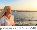 Portrait woman in a summer against the background of an evening sea 53785584